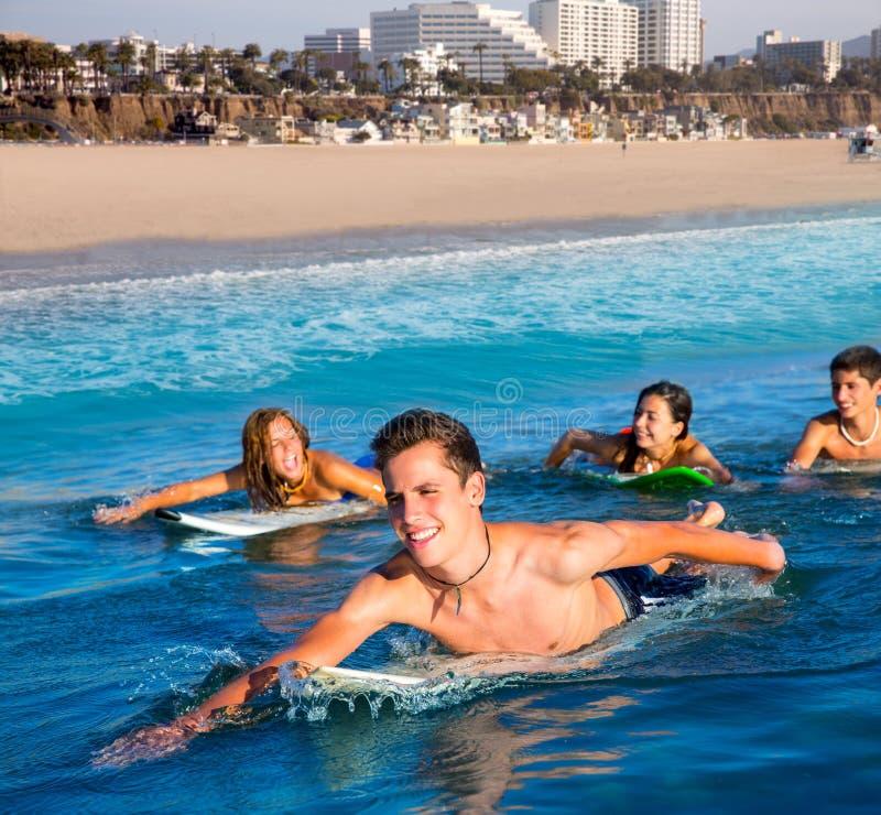 De jongens en de meisjes die van de tienersurfer ove surfplank zwemmen royalty-vrije stock afbeelding