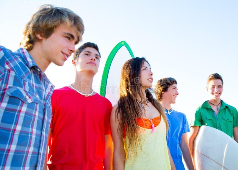 De jongens en de meisjes van tienersurfers groeperen gelukkig stock afbeelding