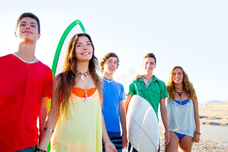 De jongens en de meisjes van tienersurfers groeperen gelukkig stock fotografie
