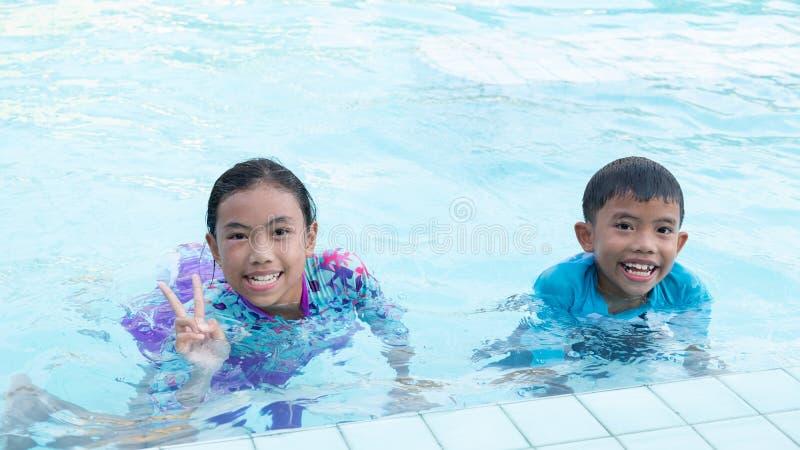 De jongens en de meisjes hebben pret het spelen in de pool stock foto