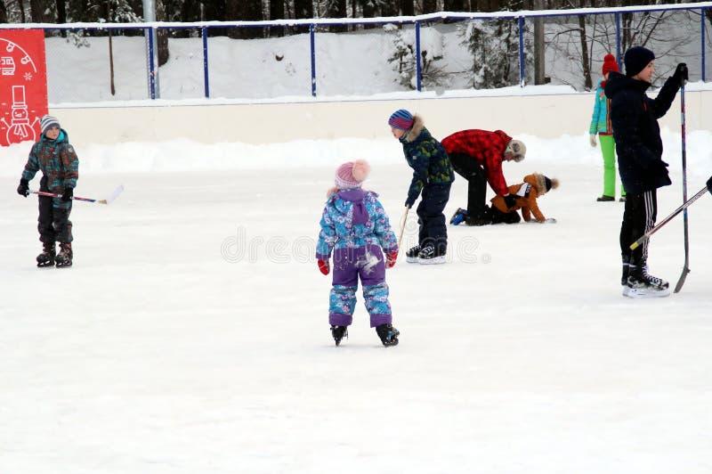 De jongens ijshockey spelen, en de meisjes die schaatsen op de openluchtpiste stock fotografie