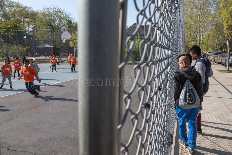 De jongens letten op de voetbal van het kinderenspel stock afbeeldingen