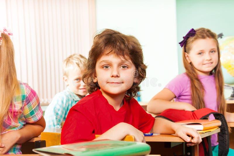 De jongens met één meisje kijken recht en zitten bij bureaus stock foto