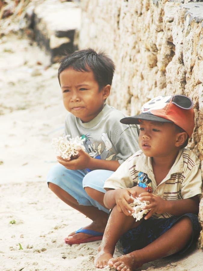De jongens proberen om kroonslak aan toeristen, Indonesië te verkopen stock fotografie