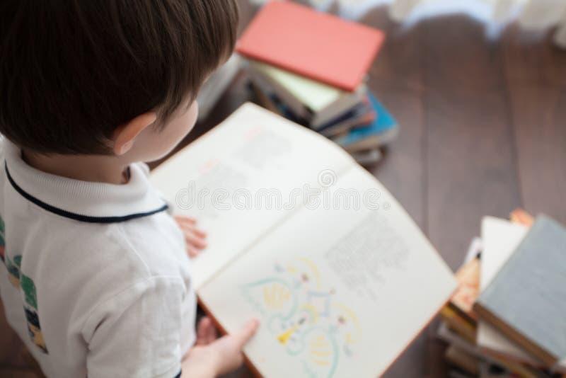 De jongens` s rug en een open boek stock afbeelding