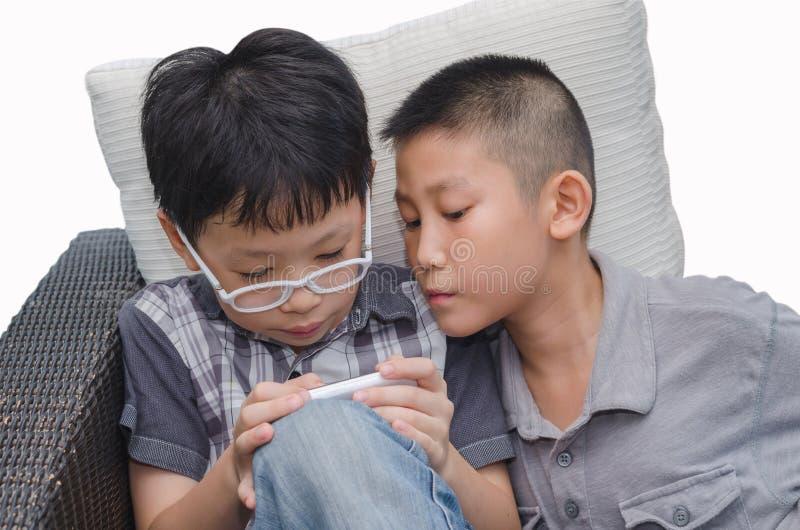 De jongens spelen spel op telefoon stock foto's