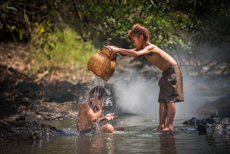 De jongens spelen in water stock afbeeldingen