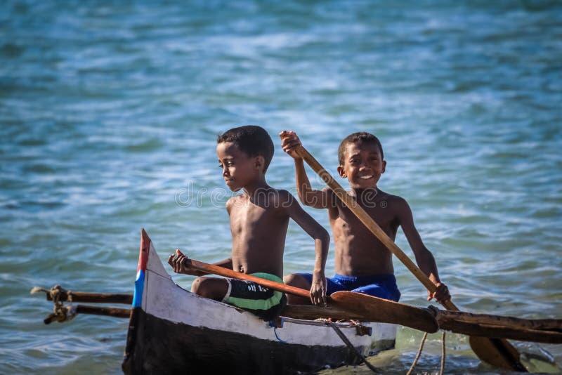De jongens van Madagascar in een boot stock foto
