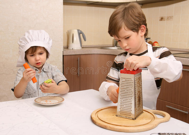 De jongens wrijven wortelen stock fotografie