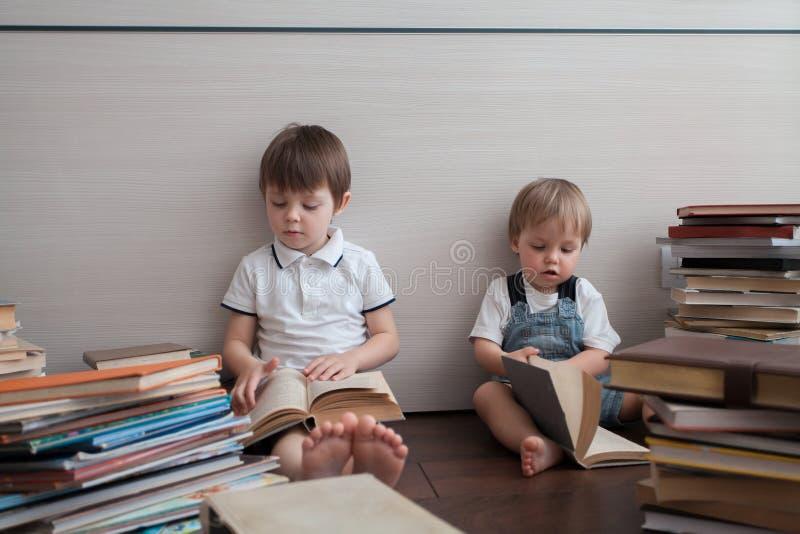 De jongens zitten dichtbij de muur met boeken stock foto