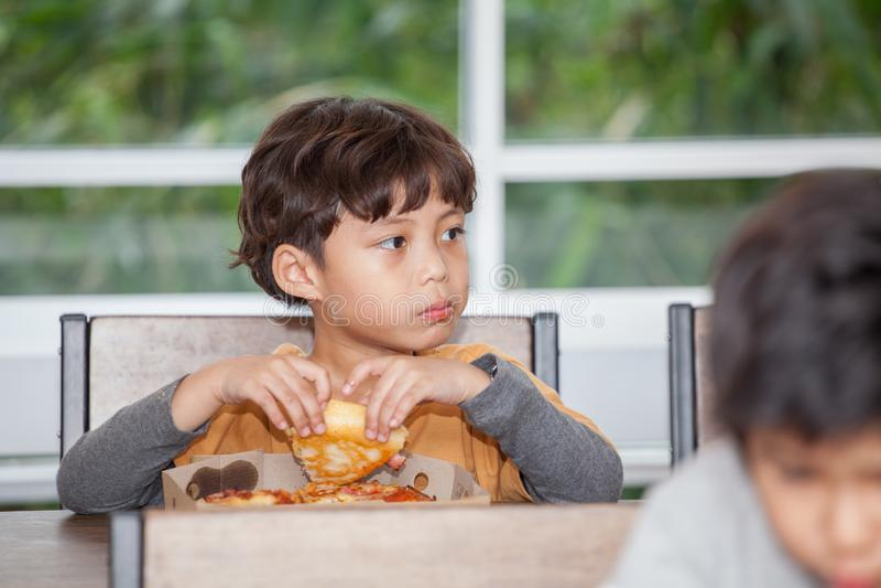 de jongenskinderen genieten van etend pizza in klaslokaalschool hongerig jong geitje stock foto's