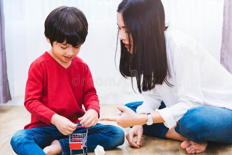 De jongenskleuterschool van het babykind het spelen stuk speelgoed met mooie moeder stock afbeeldingen