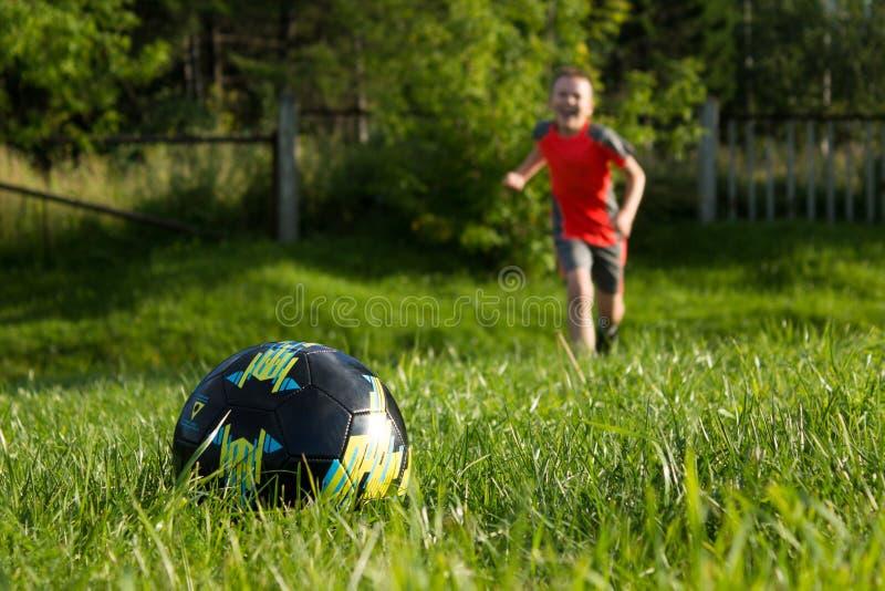 De jongenslooppas aan de voetbalbal royalty-vrije stock foto