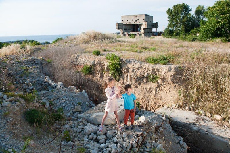 De jongensmeisje van twee slecht vluchtelingskinderen bij ruïnes de bouw vernietigd door aardbeving royalty-vrije stock foto's