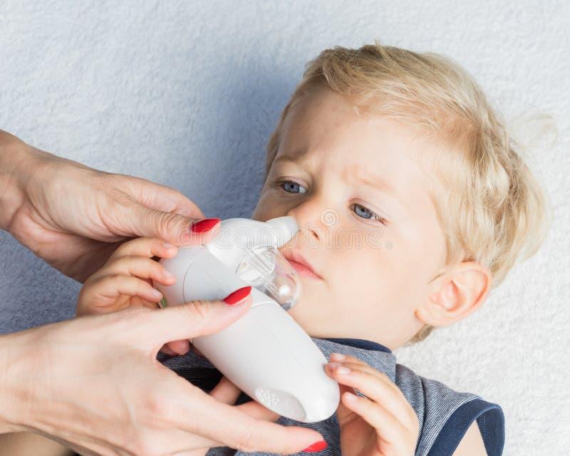 De jongensneus van de moeder schoonmakende baby stock afbeeldingen