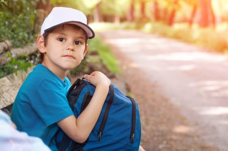 De jongensreiziger met een rugzak en een GLB zit door de weg royalty-vrije stock foto's