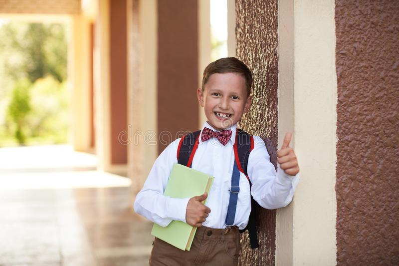 De jongensschooljongen een handboek houden die leunend tegen de muur van de school toont een handteken die van goedkeuring zijn v royalty-vrije stock fotografie