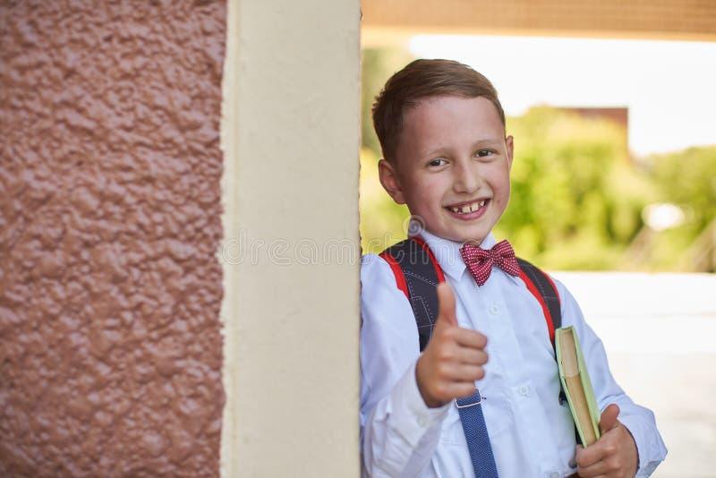 De jongensschooljongen een handboek houden die leunend tegen de muur van de school toont een handteken die van goedkeuring zijn v stock foto's