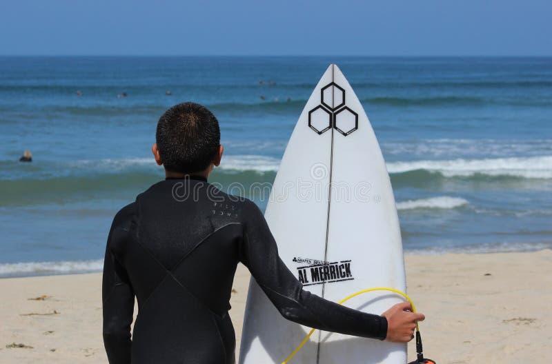De jongenssurfer bekijkt golven stock foto's