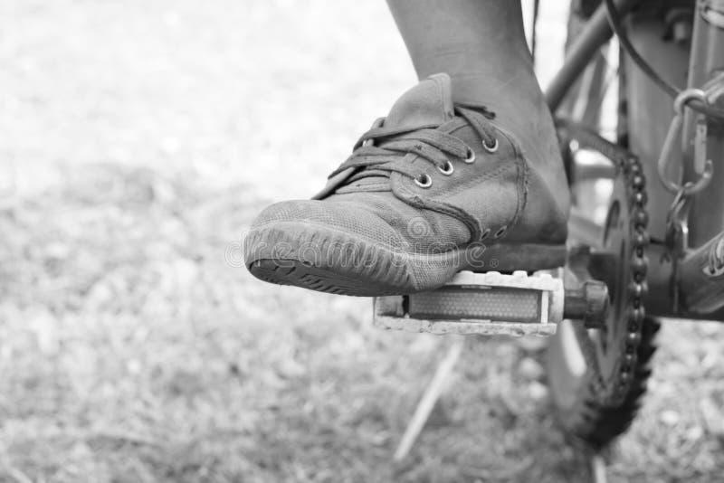 De jongensvoet op pedaal van fiets stock fotografie