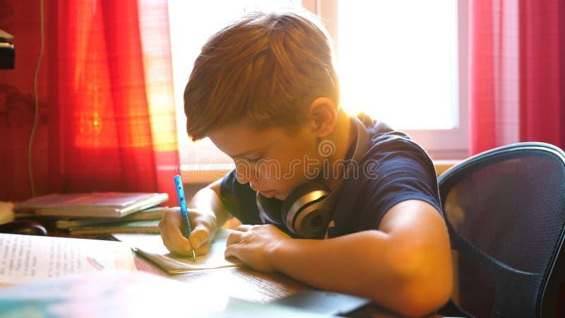 De jongenszitting bij schoolbank en doet het werk Schoolonderwijs De zon` s stralen door het glas stock afbeeldingen