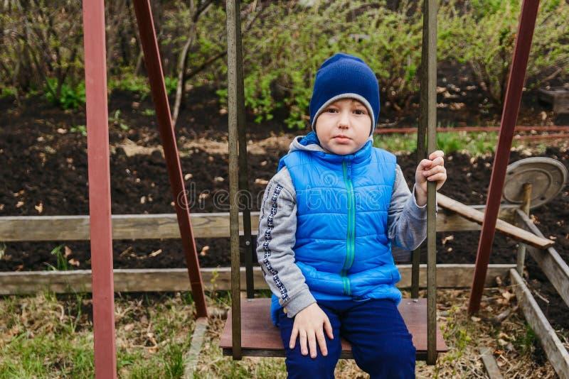 De jongenszitting op de ijzerschommeling in de tuin in de lente royalty-vrije stock fotografie