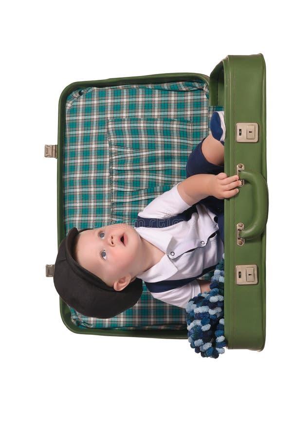 De jongenszitting van de baby in groene koffer royalty-vrije stock fotografie