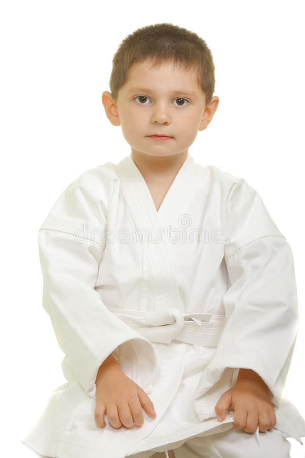De jongenszitting van de karate op knieën stock foto