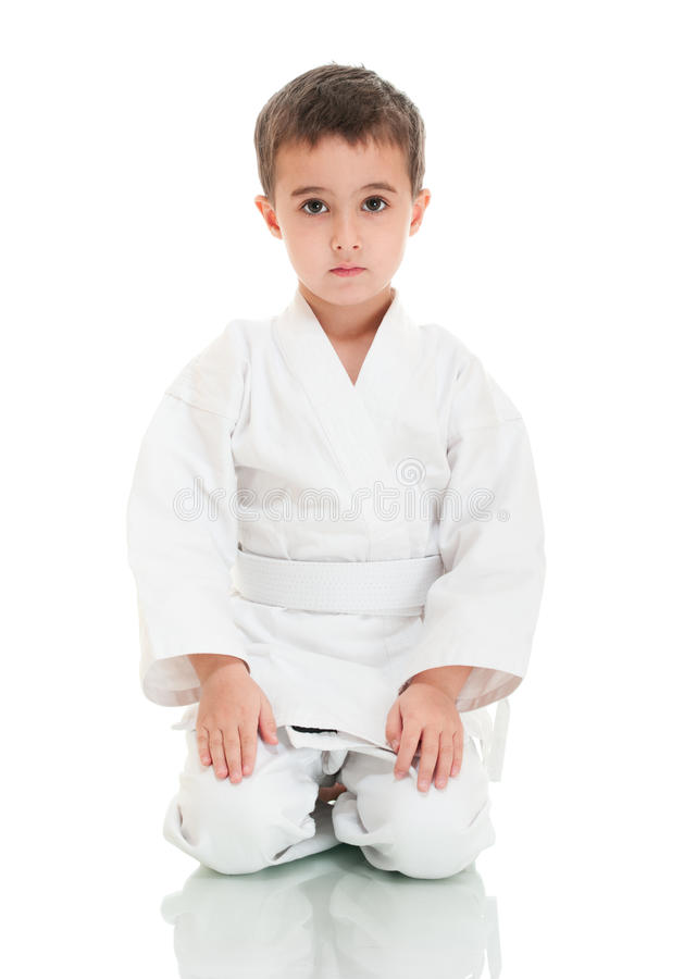 De jongenszitting van de karate in witte kimono stock fotografie