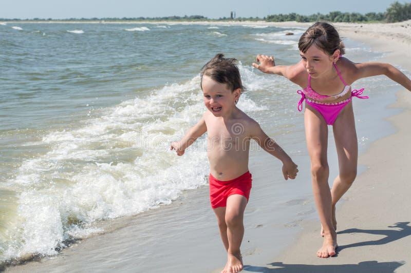 De jongere broer en de oudere zuster spelen vliegende vliegtuigen op de kust royalty-vrije stock fotografie