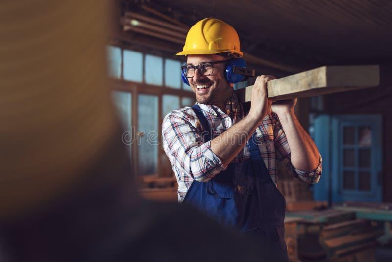 De jongere timmerman houdt houten planken royalty-vrije stock afbeeldingen