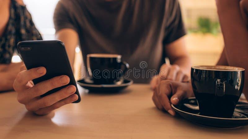 De jongeren bij koffie winkelt met telefoon royalty-vrije stock afbeeldingen