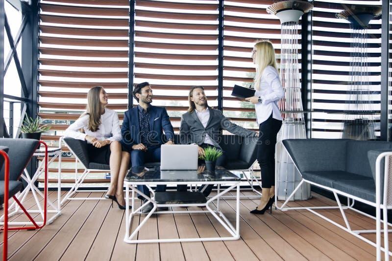 De jongeren groepeert zich in modern bureau hebt teamvergadering en hersenen stock foto