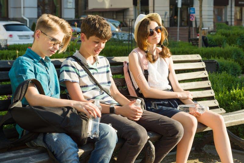 De jongeren hebt pret in de stad, spreekt de groep gelukkige tieners, het lachen, lopend genietend van dag stock foto's