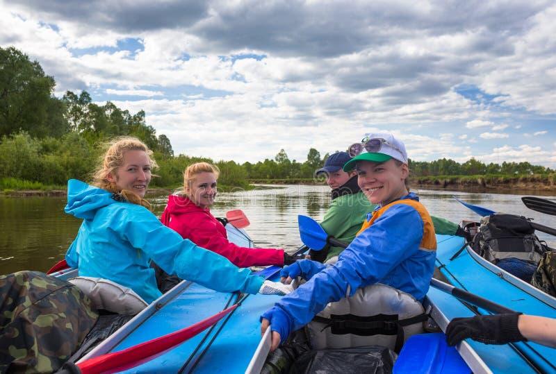 De jongeren kayaking op een rivier in mooi royalty-vrije stock afbeelding