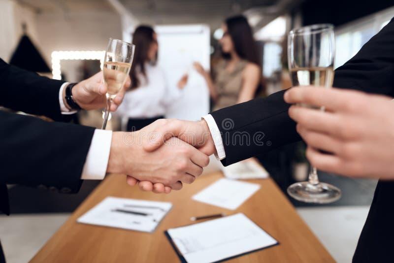 De jongeren in kostuums draagt alcoholische dranken na een commerciële vergadering stock afbeeldingen