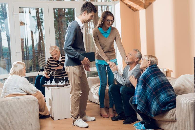 De jongeren kwam de oudere man en de vrouw in een verpleeghuis bezoeken royalty-vrije stock afbeeldingen