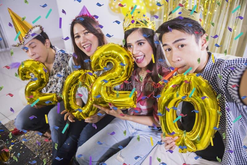De jongeren neemt foto met nummer 2020 stock fotografie