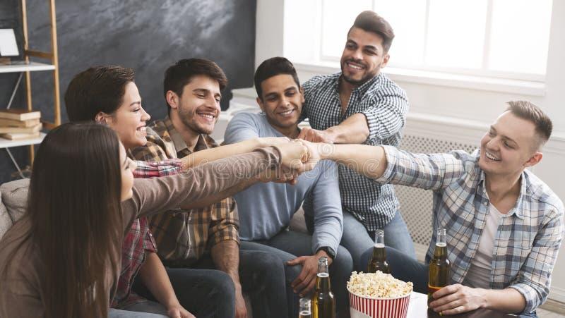 De jongeren sluit zich aan samen bij vuisten als symbool van sterke vriendschap royalty-vrije stock afbeeldingen