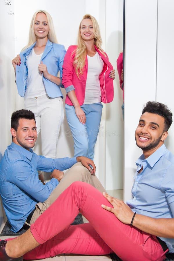 De jongeren vormt de Zaal van de Winkelmontage Winkelend, Gelukkige Glimlachende Vrouw die Nieuwe Kleren, Man Sit On Floor prober royalty-vrije stock afbeelding