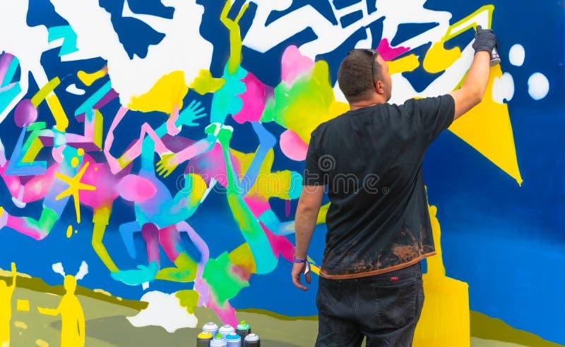 De Jongeretekening met nevels - Graffitikunstenaar het schilderen met de blikken van de aërosolkleur op de muur stock foto's