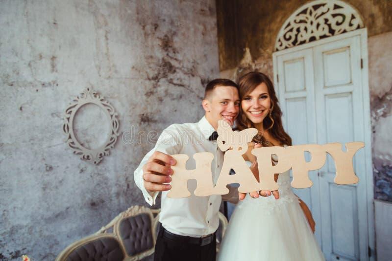 De jonggehuwden bereiken uit hun handen met het houten GELUKKIG van letters voorzien stock afbeelding