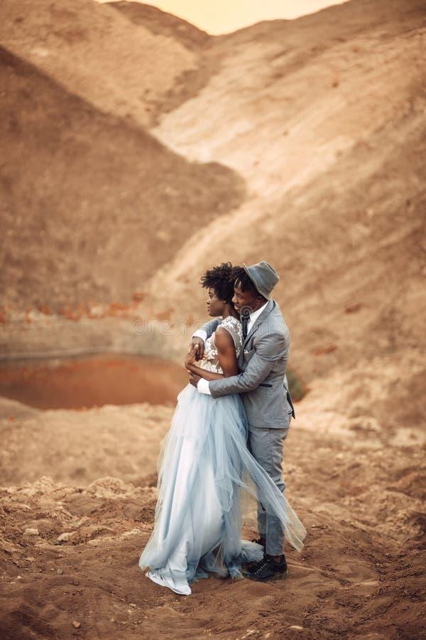 De jonggehuwden bevinden zich en omhelzing in canion tegen achtergrond van rivier royalty-vrije stock fotografie