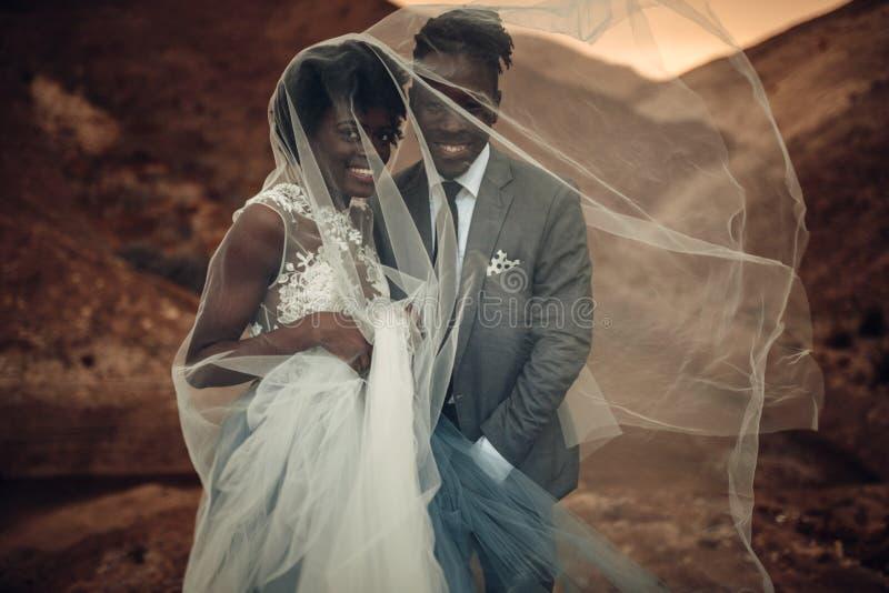 De jonggehuwden bevinden zich onder bruidssluier en glimlach in canion bij zonsondergang royalty-vrije stock afbeeldingen