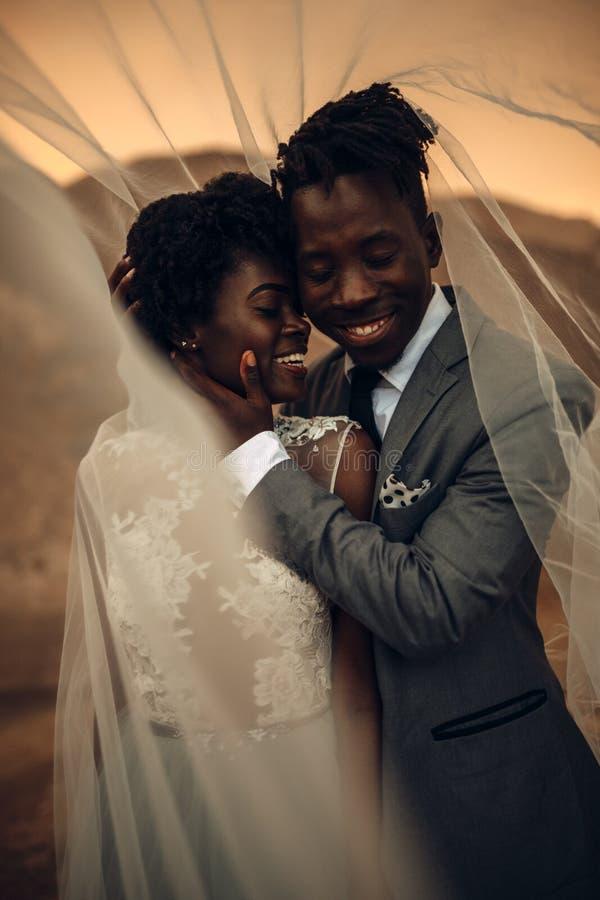 De jonggehuwden bevinden zich onder bruidssluier, omhelzen en glimlachen in canion a stock foto