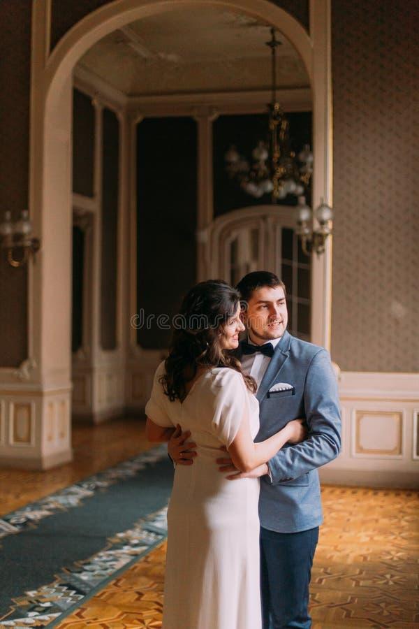 De jonggehuwden hebben een zoet teder ogenblik in de luxueuze uitstekende zaal royalty-vrije stock foto