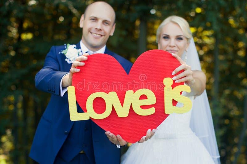 De jonggehuwden houden een rood hart royalty-vrije stock foto's
