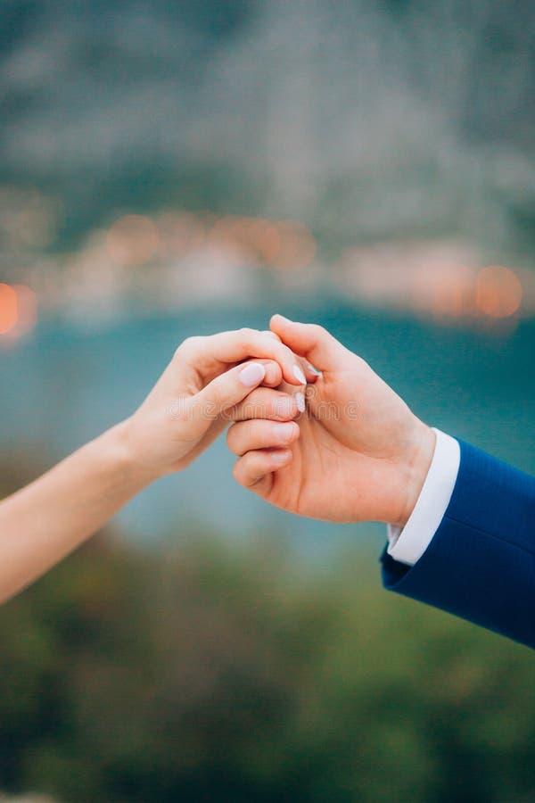 De jonggehuwden houden handen Koppel holdingshanden Huwelijk in Monte royalty-vrije stock foto
