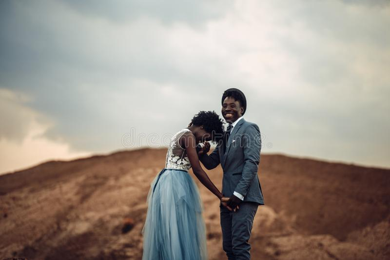 De jonggehuwden houden handen, lachen en bevinden zich tegen mooi landschap stock foto