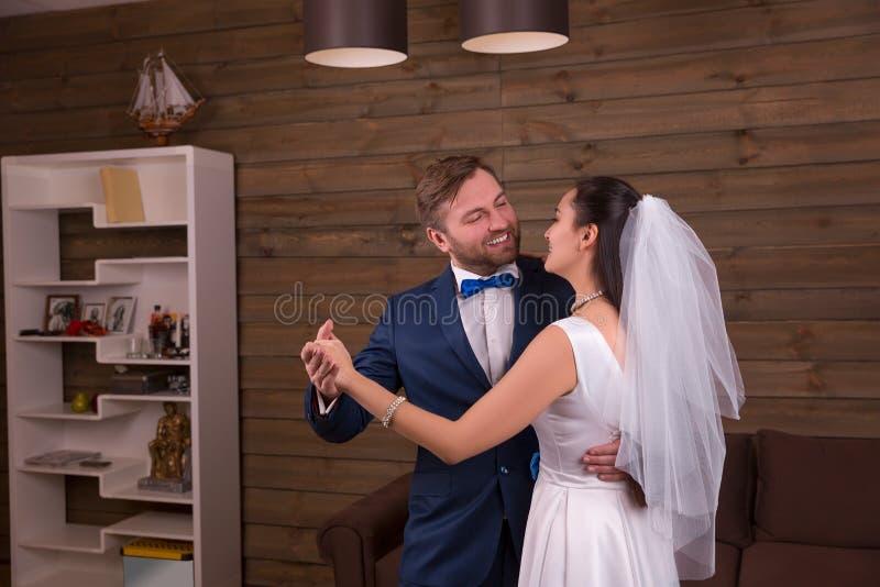 De jonggehuwden koppelen het dansen huwelijksdans stock afbeelding